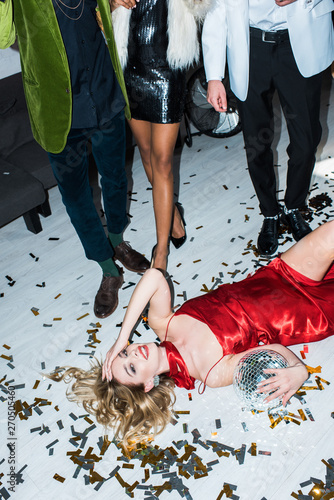 attractive and drunk blonde girl in red dress lying on floor with confetti and holding disco ball near friends - 270505460