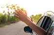 Man feeling the wind through his hands while driving in the country side.(freedom concept)