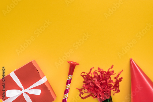 Top view of red gift box, party horn and party hat on yellow background