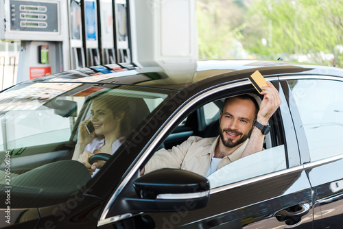 Fotografie, Obraz  happy man holding credit card while driving car at gas station