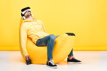 Man On Bean Bag Chair With Joystick In Virtual Reality Headset On Yellow