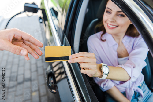 Fototapeta  selective focus of cheerful woman sitting in car and giving credit card to worke