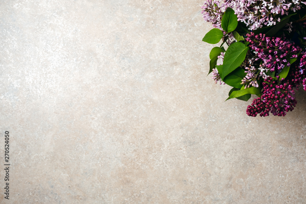 Flower frame of purple lilac bunch on concrete stone surface background. Flat lay, top view, minimal style concept. Greeting card or web banner mockup for wedding anniversary, birthday, womens day.