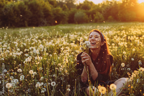 Valokuva Beautiful Young Woman lying on the field in green grass and blowing dandelion