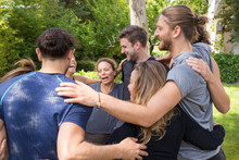 Group Of Happy People Embracing Each Other After Workout. Men And Women In Fitness Apparels Forming Circle And Hugging In Park. Fitness And Teambuilding Concept