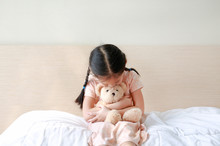 Peaceful Asian Little Girl Embracing Teddy Bear While Sitting On The Bed At Home.