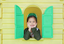 Smiling Little Asian Child Girl Playing With Window Toy Playhouse In Playground.
