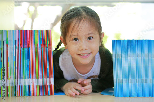 Photo sur Toile Les Textures Happy little Asian child girl lying on bookshelf at library. Children creativity and imagination concept.
