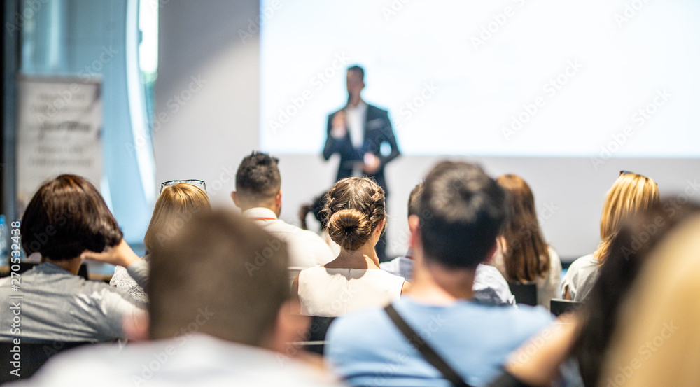 Fototapeta Male speaker giving a talk in conference hall at business event. Audience at the conference hall. Business and Entrepreneurship concept. Focus on unrecognizable people in audience.