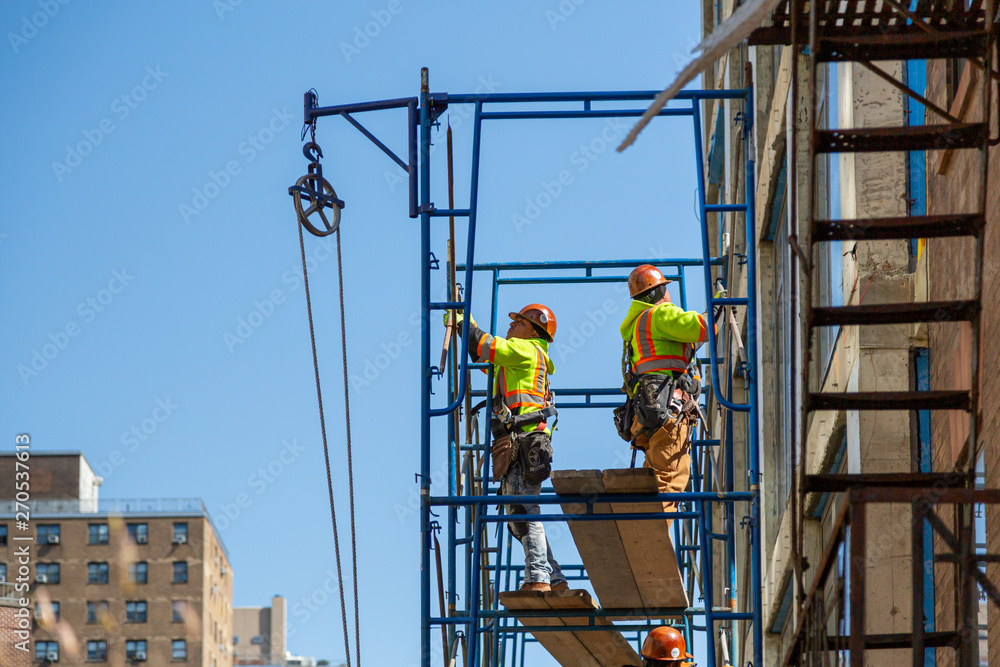 Fototapety, obrazy: Construction workers at work on a skyscraper building renovation and construction site on a scaffold