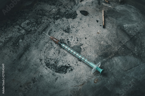 Photo  Heroin syringe on rough concrete, dirty background
