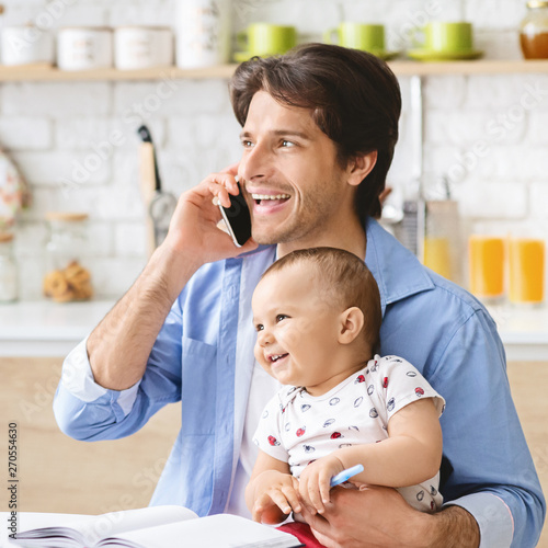 Photo Young man talking on phone at home office and take care of baby