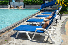 Blue Sunbeds With Mattress On Side Of Swimming Pool
