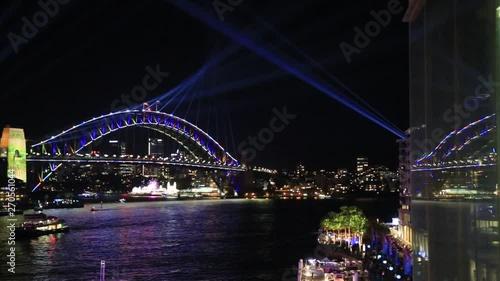 Obraz na plátně Arch of Sydney Harbour bridge and light show reflecting in glass during Vivid Sydney light show