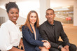 Portrait of three happy young partners or colleagues sitting together and looking at camera. Multiethnic business team in office. Team concept