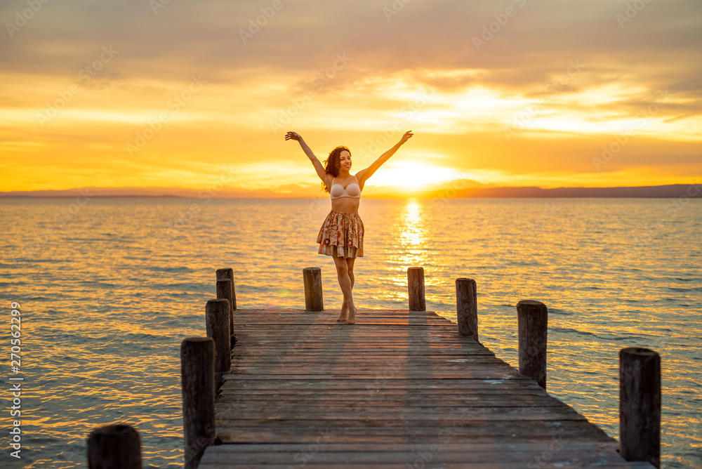 Fototapety, obrazy: Happy woman enjoying the summery sunset at the lake on her vacation. The woman in bra and a short summer skirt laughs and puts her arms in the direction of the sky