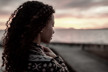 Thoughtful Evening Mood With A Young African American Woman Standing On The Promenade By The Lake And Looking Towards The Water And The Setting Sun. Photo Slightly Desaturated