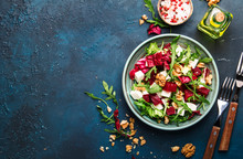 Beet Summer Salad With Arugula, Radicchio, Soft Cheese And Walnuts On Plate With Fork, Dressing And Spices On Blue Kitchen Table, Copy Space, Top View