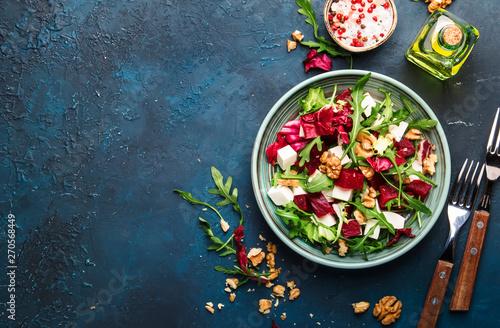 Fototapeta Beet summer salad with arugula, radicchio, soft cheese and walnuts on plate with