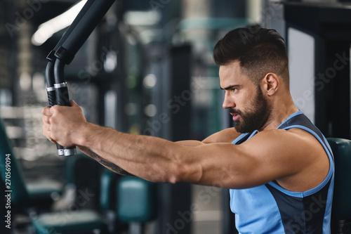 fototapeta na drzwi i meble Focused athlete exercising on training machine at gym