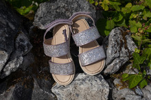 A Pair Of New Looking Abandoned Girl's Sparkly Sandals Left Behind On A Rocks, Nobody In The Image