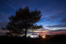 Group Of Five Young Tourists Sitting On Sea Shore Around Campfire Near Tent Under Big Tree And Blue Evening Sky With First Stars At Sunset. Tourism, Friendship Camping And Beauty Of Nature Concept.