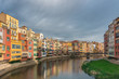 Colorful yellow and orange houses reflected in water in river Onyar. Girona, Catalonia, Spain.
