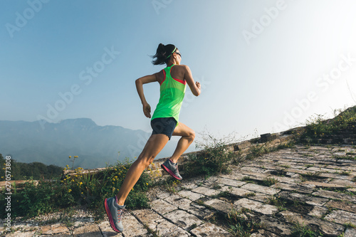 Fotografia, Obraz  Fitness running woman trail runner on the great wall top of mountain