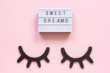 Lightbox Text Sweet Dreams And Decorative Wooden Black Eyelashes, Closed Eyes On Pink Paper Background. Concept Good Night Greeting Card Top View Creative Flat Lay