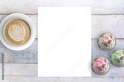 Photo  Letter paper next to some cupcakes and a mug with coffee