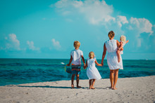 Mother With Son And Daughters Walk On Beach