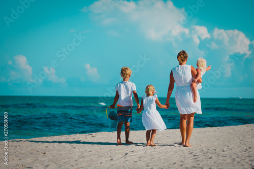 Photo sur Toile Les Textures mother with son and daughters walk on beach