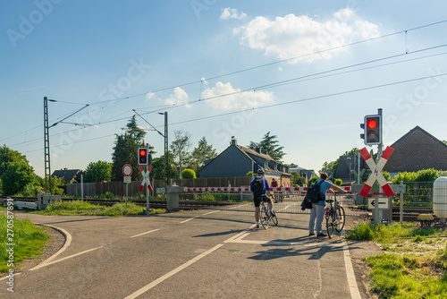 Valokuva  Outdoor sunny view of peoples after work commute and stop at level crossing railway barrier wait for a train and green light in small village countryside in Meerbusch, Germany