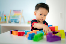 Adorable Asian Toddler Baby Boy Sitting On Chair And Playing With Color Block Toys At Home..