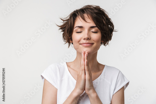 Portrait of joyous woman with short brown hair in basic t-shirt keeping palms together and praying