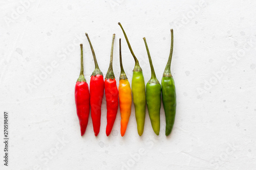 Foto auf AluDibond Hot Chili Peppers Red Hot Chili Peppers On Background or White Table. A Lot of Red Chilli Peppers. Green, Yellow Hot Chili Peppers. Copy space for your text. Flat lay, top view. Colorful chili pepper rainbow. Gradient