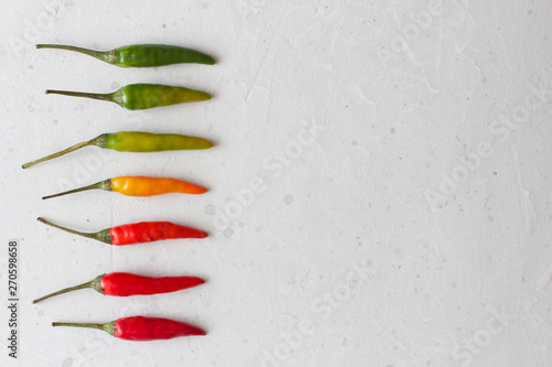 Deurstickers Hot chili peppers Red Hot Chili Peppers On Background or White Table. A Lot of Red Chilli Peppers. Green, Yellow Hot Chili Peppers. Copy space for your text. Flat lay, top view. Colorful chili pepper rainbow. Gradient