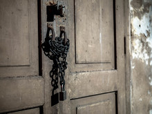 Old Wooden Door Locked With Rusty Chain And Padlock.