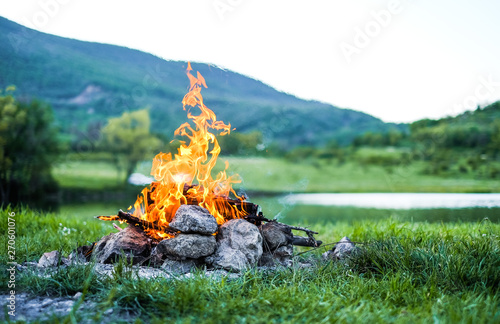 Obraz Burning fire in nature on the background of the lake The embers in the fire. Burning coal in the bonfire.  - fototapety do salonu