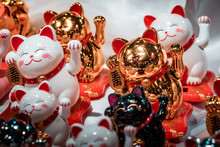 Fortune Cats. Oriental Souvenirs, Mass Produced For International Export And Trade. Close Up Shot, Artificial Lighting. Concept Image For Economic War Between China And America.