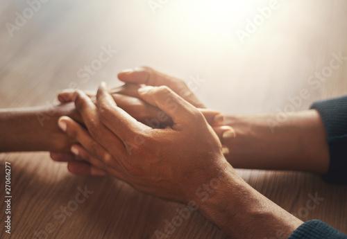 Fotografering  Couple's hand holding hands on wooden desk