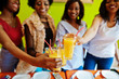 Four young african girls in bright colored pizza restaurant clinking juices.
