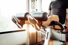 Close Up Of Man Lifting Weight By Two Legs For Stretching Muscle At Fitness Gym At Private Condominium Background. Sport And People Lifestyles Concept.
