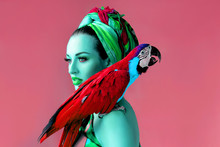 Ultraviolet Portrait Of Young Attractive Woman In African Style Holding Ara Parrot On Her Hand On Bright Background