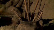 Close-up Low-angle Tilting Shot Of An Ancient Ceramic Pot With Broken Cooking Sticks Inside A Cemetery Cave, Altiplano, Bolivia