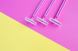 canvas print picture - Three women's razors pink on an isolated pink and yellow background.