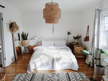 Bedroom Setup With Large Mirror, Snake Plant And Sun Hats With Wicker Light