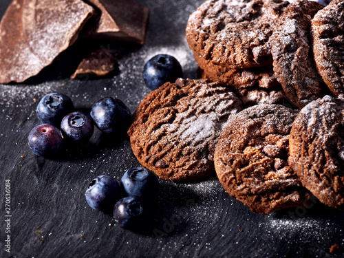 Serving food on slate onto wooden table. Oatmeal cookies biscuit with blueberry on picnic dark tiles countrylike. Chocolate chip cookies tied with string. Dessert in cafe.