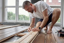 Concentrated Man Planing Wooden Board At Home
