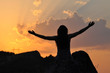 Beautiful woman raise hands and enjoy in sunset. Woman on top of mountain at sunset